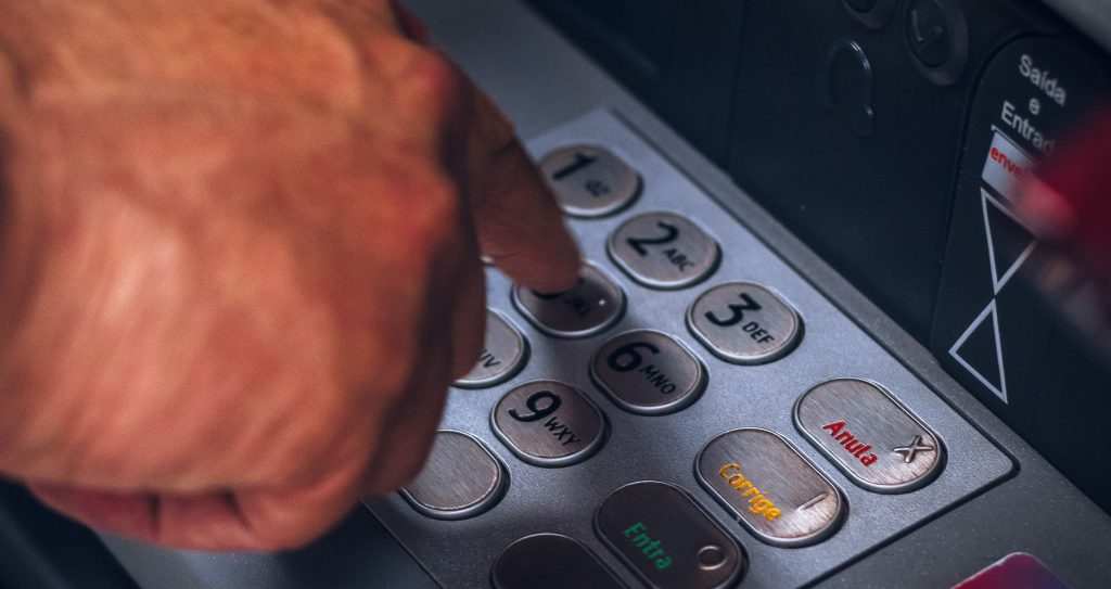 Man entering his PIN into an EMV certified payment terminal.